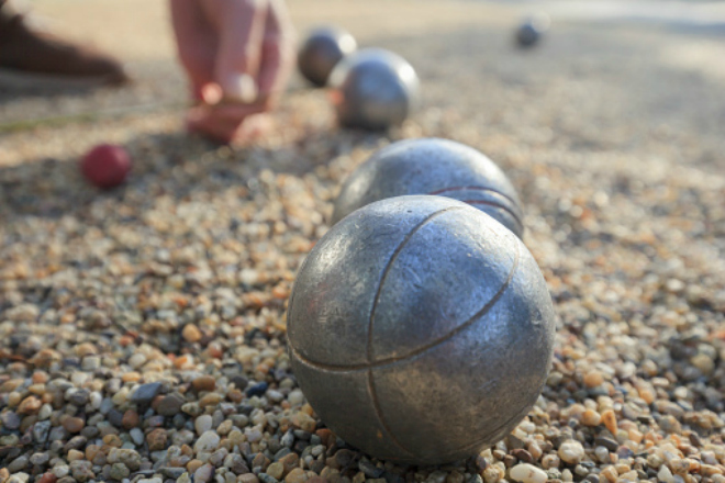 measuring the distance between metallic petanque balls and a small red jack on fine gravel