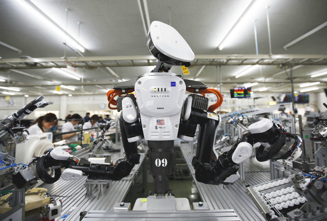 A humanoid robot works side by side with employees in the assembly line at a factory of Glory Ltd., a manufacturer of automatic change dispensers, in Kazo, north of Tokyo, Japan, in this July 1, 2015 file photo. Glory is in the vanguard as Japanese firms ramp up spending on robotics and automation, responding at last to premier Shinzo Abe's efforts to stimulate the economy and end two decades of stagnation and deflation. REUTERS/Issei Kato/Files