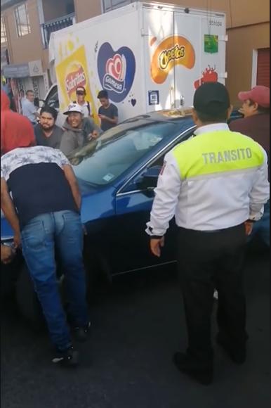 Mujer se estaciona a media calle y conductores cargan su auto para orillarla